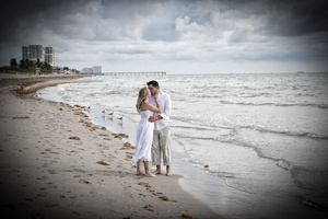 Barefoot wedding couple kissing on beach